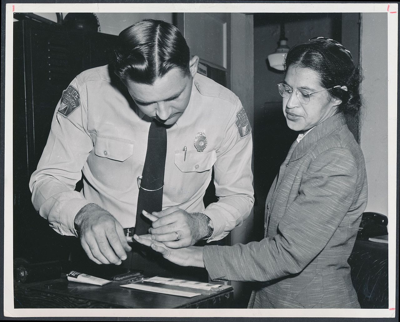 Rosa Parks being fingerprinted by Deputy Sheriff D.H. Lackey (By Associated Press (http://www.rmyauctions.com/lot-8002.aspx) [Public domain], via Wikimedia Commons)